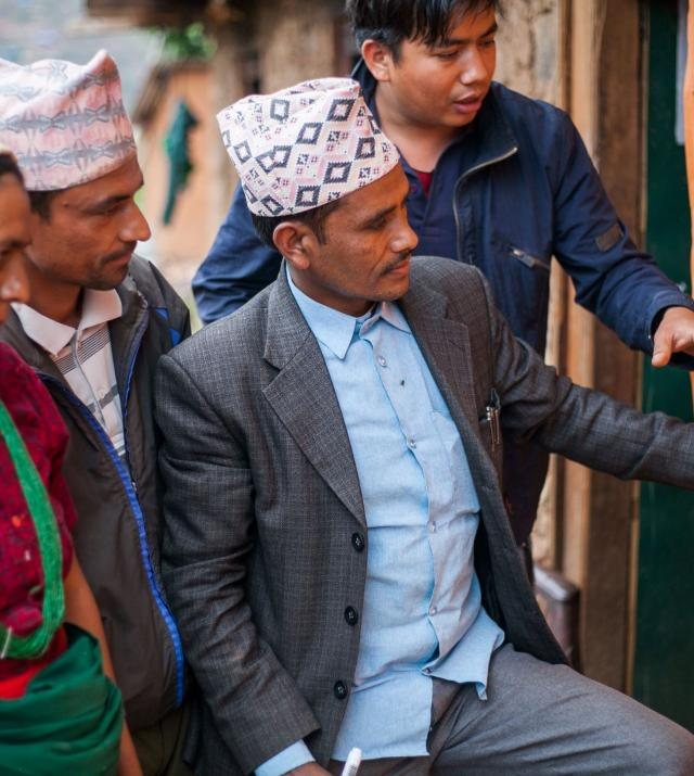 Photo of three Nepalese men and one woman looking and pointing to a posterboard