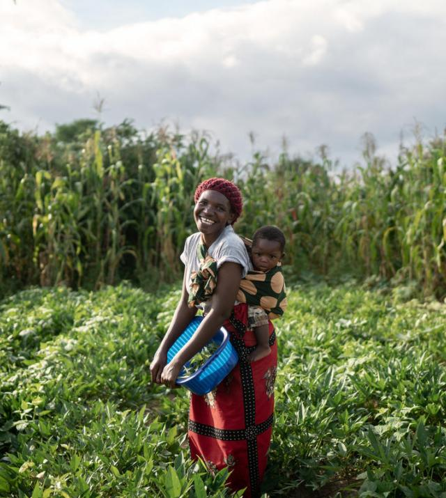Photo of a woman carrying a child standing in a field.