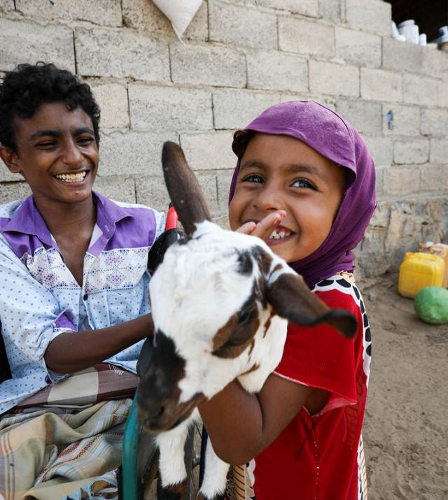 children smiling while holding a goat