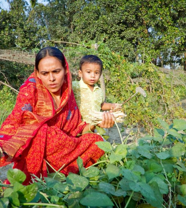 woman farming holding a child in her arms
