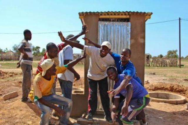 men in front of latrine
