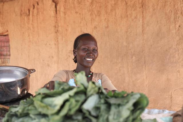 photo of a woman smiling behind a market stall